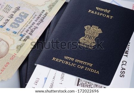 view of indian passport with airline boarding pass and some cash. - stock photo