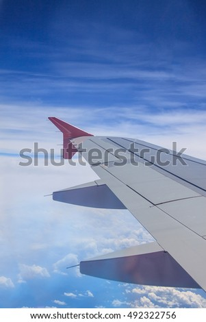 view of jet plane wing with cloud and blue sky
