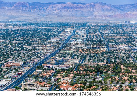 View of Las Vegas from the roof of a hotel looking out towards the mountains.  - stock photo
