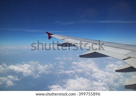 View of left wing plane in blue sky.