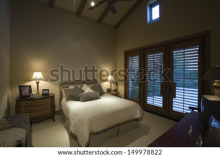 View of lit lamps by tidy bed - stock photo