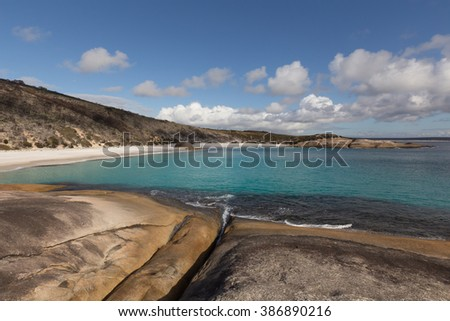 View of Little Beach from Flat Rocks under Cloudy Blue Sky on a Sunny Day - stock photo
