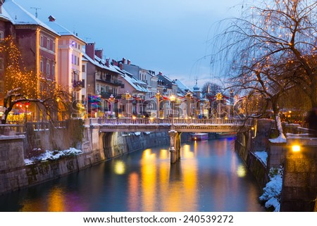 View of lively river Ljubljanica bank with Cobblers' Bridge in old city center decorated with Christmas lights. Ljubljana, Slovenia, Europe. Shot at dusk. - stock photo