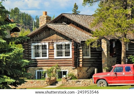 View of log house and red truck on sunny summer day in Canada - stock photo