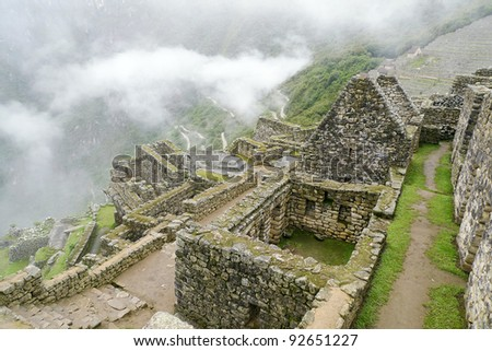 View of lower urban residential district at Machu Picchu complex. Hiram Bigham highway can be seen in the background climbing the steep mountainside. Machu Picchu, Peru. - stock photo