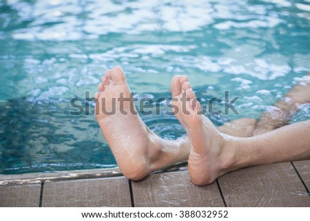 View of male feet in the pool - stock photo
