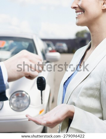 view of man in car dealership giving car keys to client