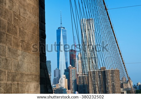 View of Manhattan City Skyline Featuring One World Trade Center Skyscraper on Sunny Day with Blue Sky, New York City, New York, USA as seen from Brooklyn Bridge Pedestrian Walkway - stock photo