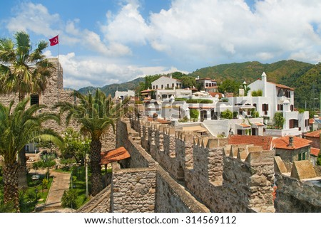 view of Marmaris castle with Turkish flag and white houses in old town with green mountains at background on sunny day against blue sky, Marmaris, Turkey - stock photo