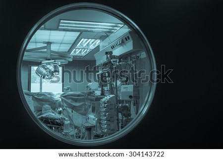 View of medical equipment through the operating room door round window. /cyanotype// - stock photo