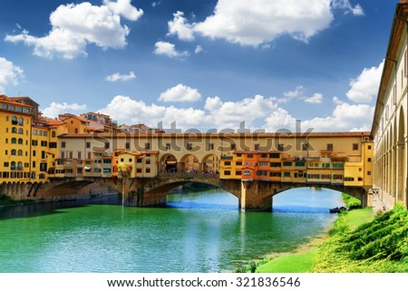 View of medieval stone bridge Ponte Vecchio (Old Bridge) over the Arno River and the Vasari Corridor in Florence, Tuscany, Italy. Florence is a popular tourist destination of Europe.