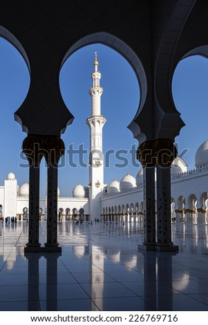 View of minaret of Sheikh Zayed Mosque through the arches in courtyard of mosque. Abu Dhabi, UAE. - stock photo