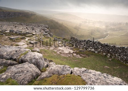 View of misty Malham Dales from limestone pavement above Malham Cove in Yorkshire Dales National Park - stock photo