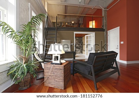 View of modern reconstructed living room with mezzanine. Close up view of Furnished area and palm tree - stock photo