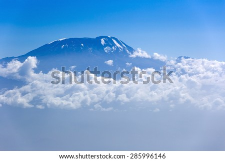 View of Mount Kilimanjaro from Mt Meru, Tanzania in Africa. Clouds surrounding the mountain.