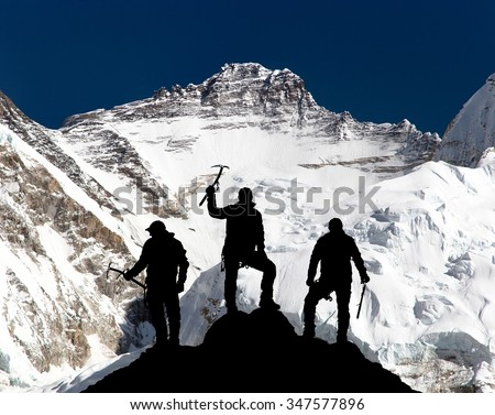 View of mount Lhotse from Pumo Ri base camp and silhouette of group of climbers with ice axe in hand, Everest area Khumbu valley, Sagarmatha national park, Nepal - stock photo