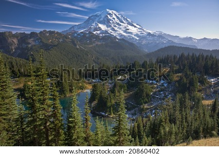 View of Mount Rainier on a clear blue day with a dusting of snow in the lower hills - stock photo