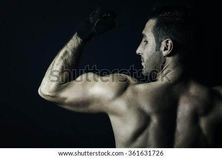 view of muscular man flexing biceps in front black background - stock photo