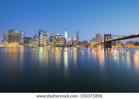View of New York City Manhattan midtown at dusk with skyscrapers illuminated over east river - stock photo