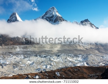 view of Ngozumba glacier with clouds and cholo peak and Kangchung Peak - Nepal - stock photo