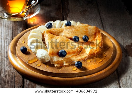 view of nice fresh hot crepes with fruit dessert  on color background - stock photo