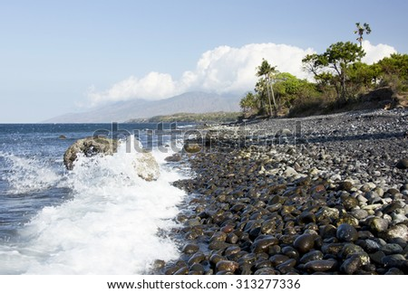 View of north east coastline of Bali Indonesia showing black volcanic rock and sand beach formed during eruption / pyroclastic flow of nearby Mount Agung with waves breaking against shore rocks  - stock photo
