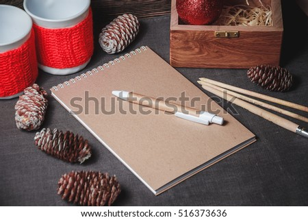 view of notebook in the center of cute red Christmas decoration, cones