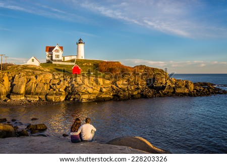View of Nubble lighthouse in Maine in New England USA showing rocky coastline against blue sky with young couple taking in the view in foreground. - stock photo