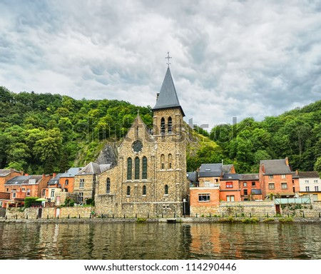 View of old church in Dinant from the river Meuse, Belgium in cloudy day with dramatic sky - stock photo