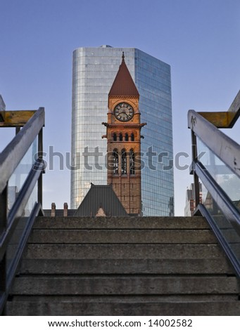 View of old historic Toronto city hall and the clock tower in front of the modern skyscraper at sunset - stock photo