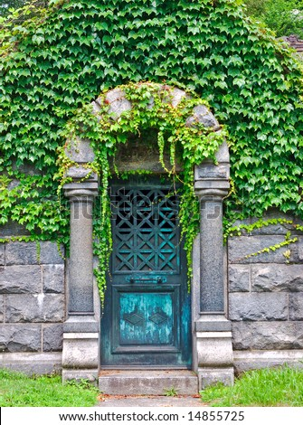 View of old mausoleum door with ivy vines.