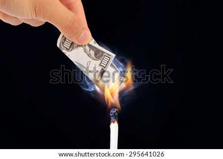 View of one hundred dollar banknote burning with a match stick, on black background. - stock photo