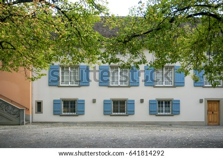 View of open windows vintage pastel building with green tree in autumn.