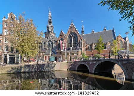 View of Oude Kerk (Old Church) from across the Oudezijds Voorburgwal canal in Amsterdam, Netherlands - stock photo