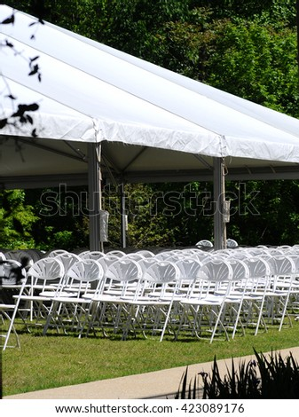 View of outdoor event seating, featuring white folding chairs under a white canopy, on a sunny day. - stock photo