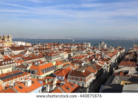 View of over the rooftops of Lisbon from the top of the Santa Justa Elevator towards the River Tagus and the Se Cathedral. - stock photo