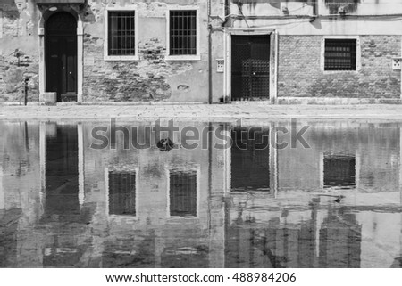 View of palaces in Campo San Polo in Venice with reflections on the water.