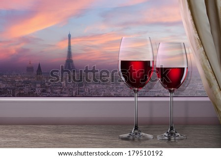 View of Paris and Eiffel tower on sunset from window with two glasses of wine - stock photo