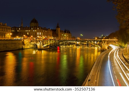 View of Paris by night with a bridge over the Seine river and the Conciergerie building near Notre-Dame - stock photo