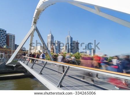 View of people in motion blur walking across the Southgate footbridge in Melbourne during daytime  - stock photo