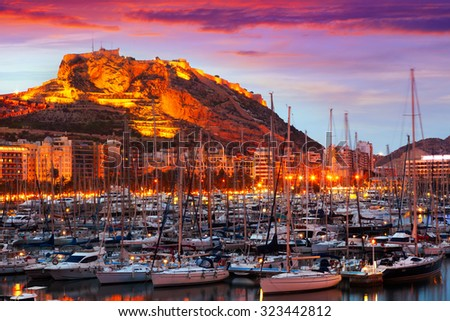 View of port with yachts against Castle on mount in background during sunset. Alicante, Spain - stock photo