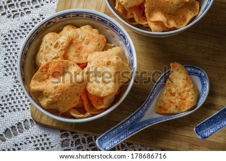 View of potato chips in bowls on hand knitted tablecloth background