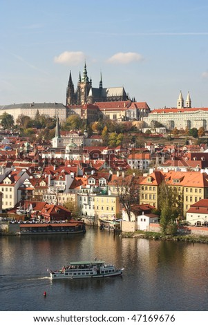 View of Prague with castle and tourboat on the river