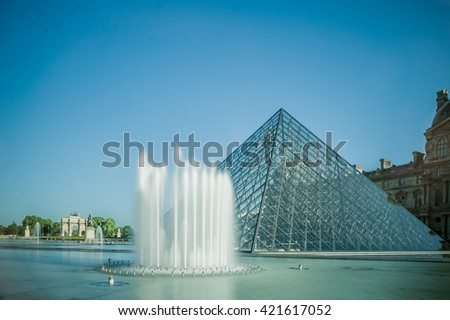 View of pyramid and fountain at courtyard of Louvre Museum.  Louvre Museum is one of the largest and most visited museums worldwide. - stock photo