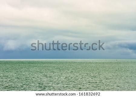 view of rain cloud over ocean - stock photo