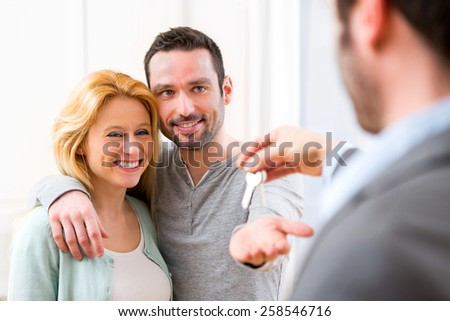 View of Real estate agent delivers keys of new house to young couple - stock photo