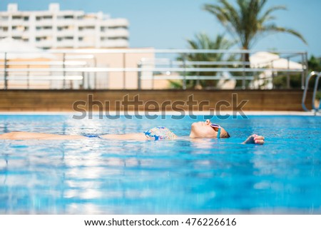 View of relaxed woman in sunglasses floating in bright pool water in sunlight