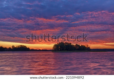 View of rippled water surface and cloudy sky just before sunrise, Mazury, Poland - stock photo