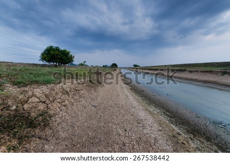 View of river, cloud and Cracked soil upon cloudy sunset. The village view where the water of river is at low level because of drought season.  There are bunch of cloud dried river and cracked soil. - stock photo