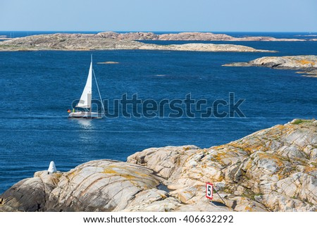 View of rocky archipelago with a sailing boat - stock photo
